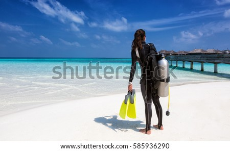 Female scuba diver with diving equipment on the beach at the Maldives #585936290