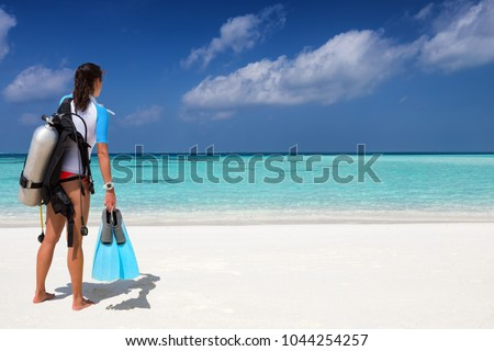 Female scuba diver with diving gear stands on a tropical beach and watches the scene #1044254257