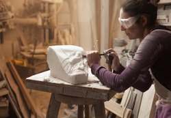 Female sculptor at work in a workshop, using hammer and chisel to sculpt a piece of white marble stone, debris and particles flying around, stonemasonry and stonecraft, copy space