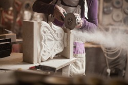 Female sculptor cutting a white marble piece with a power tool, craftswoman shaping a sculpture with an angle grinder, caucasian woman working inside an arts workshop, detail closeup of hands and dust