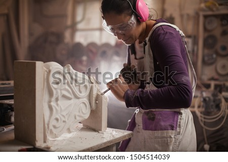 Female sculptor working on a piece using hammer and chisel, sculpting a white marble stone into a beautiful pedestal, stonemasonry and stonecraft Stock photo ©