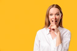 Female secret. Hush silence. Special offer. Keep quiet. Portrait of enthusiastic amazed surprised woman in white shirt showing shhh with finger at open mouth isolated on orange copy space background.