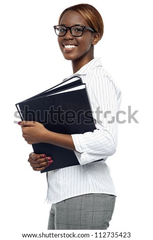Female secretary carrying office files. Looking at camera and smiling