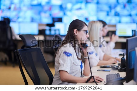 Female security guard operator talking on the phone while working at workstation with multiple displays Security guards working on multiple monitors