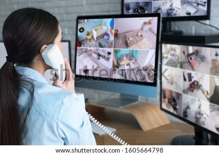 Female security guard talking by telephone near monitors at workplace Foto stock ©