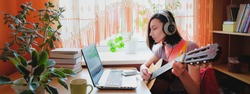 Female self education online. Woman plays guitar at front of laptop.