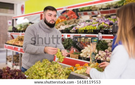 Female seller assisting customer to weigh grape