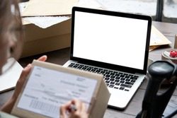 Female seller, internet shop small business owner holding ecommerce shipping box checking online store dropshipping order on mock up white blank laptop screen. E commerce post shipping delivery.