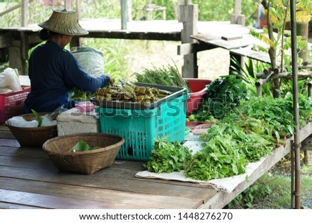Female seller sits on wooden floor and sells the organic vegetable and food in traditional market. Lifestyle and culture of market in Thailand. Freshness and clean food concept