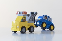 female service car driver tows away car with male driver. flirt on the street screne. made with colorful toy vehicles.