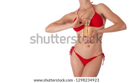 Female sexy fit body in red classic bikini with oil spray bottle, isolated on white. Woman holds an oil spay bottle. Well groomed tanned skin. Body care, beach, artificial tanning and sunprotection #1298234923