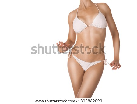 Female sexy fit body in white classic bikini, isolated on white. Woman holds panties straps. Well groomed tanned skin. Body care, beach, summer, fitness, artificial tanning and sunprotection SPF #1305862099