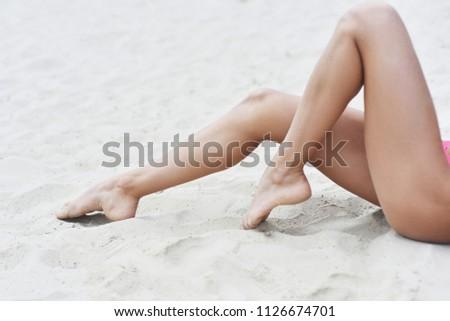 Female sexy legs on the beach. Epilation laser epilation. #1126674701