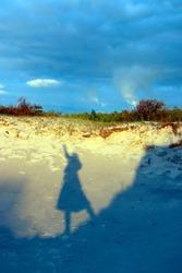 Female shadow on the sea sand.