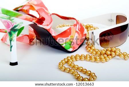 Female shoe, pearls and sunglasses
