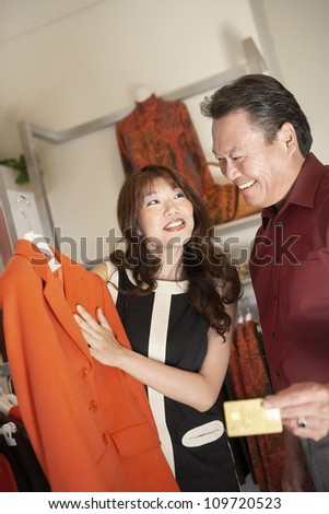 Female shop owner displaying coat to male customer