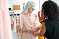 Female shop seller helping woman to try on new dress and tying waistband. Customer choosing clothes in fashion store. Buying clothes in boutique concept