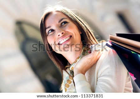 Female shopper holding shopping bags and looking happy
