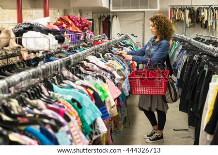Female Shopper In Thrift Store browsing through clothing #444326713