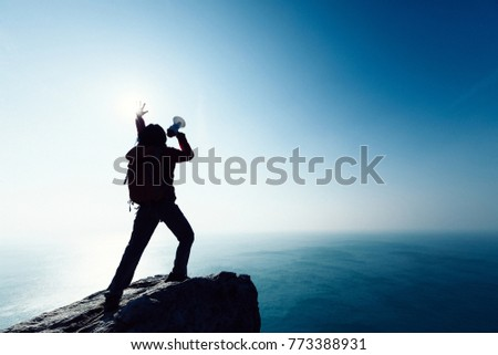 female shouting with loudspeaker on windy sunrise coast cliff edge #773388931