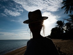 Female silhouette in hat over sky
