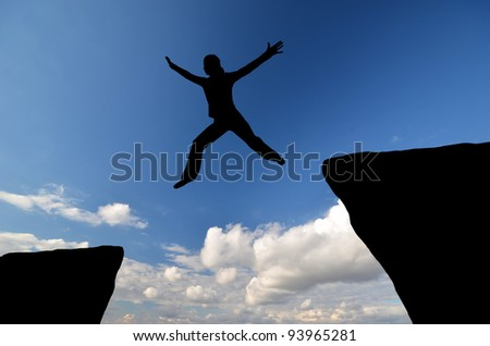 female silhouette jumping from one rock to another in the sky