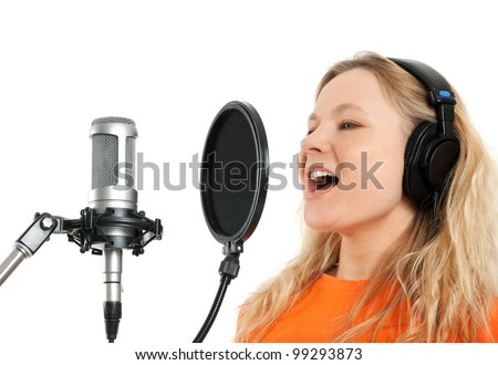Female singer in headphones singing with studio microphone. Isolated on white background. - stock photo