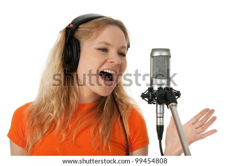 Female singer in headphones singing with the microphone. Isolated on white background.