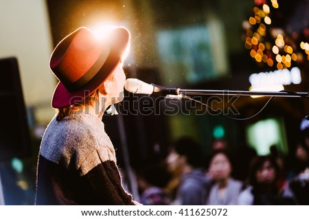 Female singer, performing her vocal sound. With lens flare and spotlight. ストックフォト ©