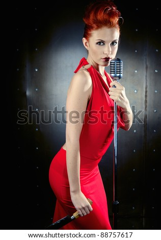 Female singer red dress with knife - stock photo