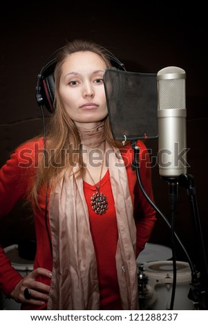 Female singer with headphones recording in studio