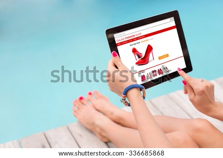 Female sitting by the pool and using technology to shop online
