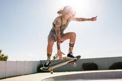 Female skater practising skateboarding at skate park. Women doing ollie on skateboard.