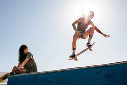 Female skater rides on skateboard with female friend sitting on ramp. Female skateboarding at skate park with friend watching the routine.