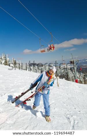 Female skier holding ski; blue jacket; horizontal orientation