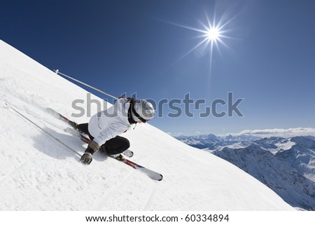 Female skier on a steep slope with mountainraing and sun in the background - stock photo