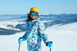 Female skier on snowy slope in mountains. Winter vacation