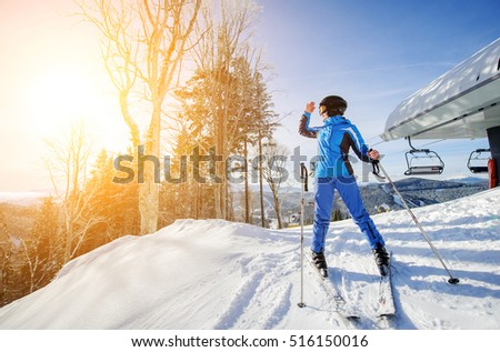 Female skier on the top of ski slope with ski-lift and mountains on the background. Winter sports concept. Girl is looking at beautiful mountain landscape on sunny day. Bukovel, Ukraine #516150016