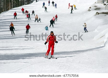 Female skier skiing down a wide track for beginners