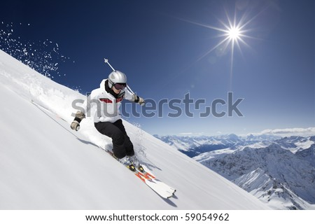 female skier skiing downhill with sun and mountains