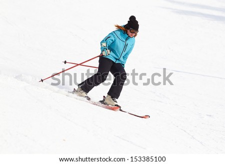 Female skier turning in deep powder with mountains valley's #153385100