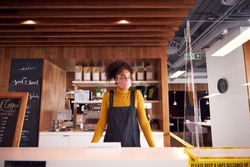 Female Small Business Owner Of Coffee Shop In Mask Standing Behind Counter During Health Pandemic