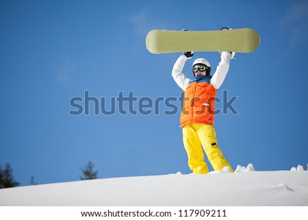 female snowboarder against sun and blue sky
