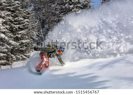 female snowboarder curved and brakes spraying loose deep snow on the freeride slope. downhill with snowboards in fresh snow. freeride world champion. swirls of snow in the air, in a bright mask #1515456767