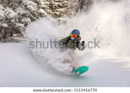 female snowboarder curved and brakes spraying loose deep snow on the freeride slope. downhill with snowboards in fresh snow. freeride world champion. swirls of snow in the air, in a bright mask