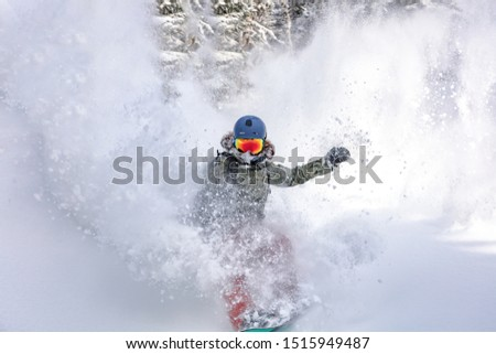 female snowboarder curved and brakes spraying loose deep snow on the freeride slope. downhill with snowboards in fresh snow. freeride world champion. swirls of snow in the air, in a bright mask #1515949487