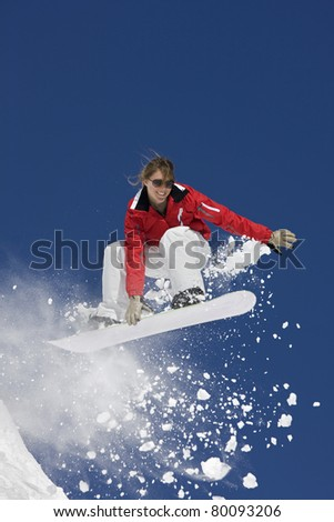 Female snowboarder in mid-air with deep blue sky in background.