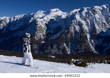 Female snowboarder is riding on snow in Dolomites