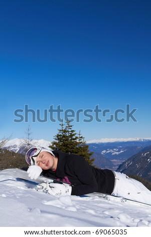 Female snowboarder is sleeping on snowboard