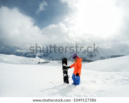 Female snowboarder standing with snowboard in her hand. Girl snowboarder posing with snowboard on background of mountain #1049127386
